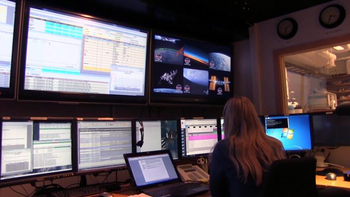 Mona Schiefloe har sittet ved denne konsollen hele dagen, og fulgt med på hva som har skjedd på romstasjonen på skjermene bak. Videolinken har vært på den seksdelte skjermen midt i bildet. (Foto: Lasse Biørnstad/forskning.no)