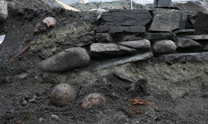 Den nordlige veggen i kirken. Med en grav i profilen, samt en beinsamling i forgrunnen. FOTO: NIKU