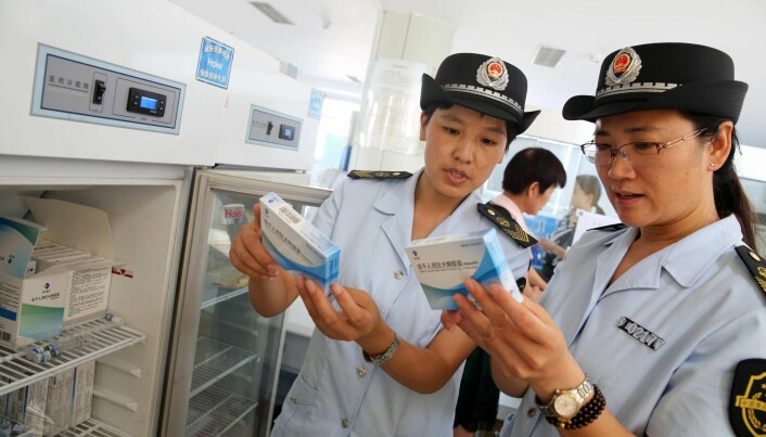 Bildet viser ansatte ved den statlige mat- og legemiddeletaten i Kina som undersøker vaksiner mot rabies. Et stort legemiddelfirma måtte betale bot på over en milliard etter at det ble kjent at over hundre tusen doser var falske. (Foto: AFP)