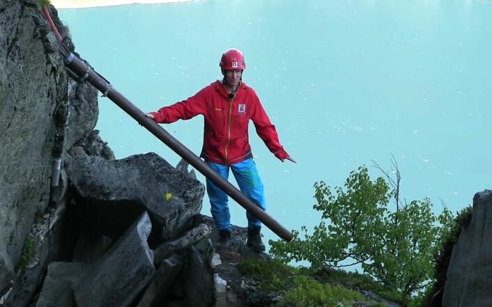 Strekkstag kan måle bevegelser i fjellsprekker. Lars Harald Blikra viser hvordan staget er festet. Til venstre er fst fjell, til høyre er løst fjell som beveger seg ned mot fjorden. Fra en video laget av NVE. Se videoen her! (Foto: NVE)