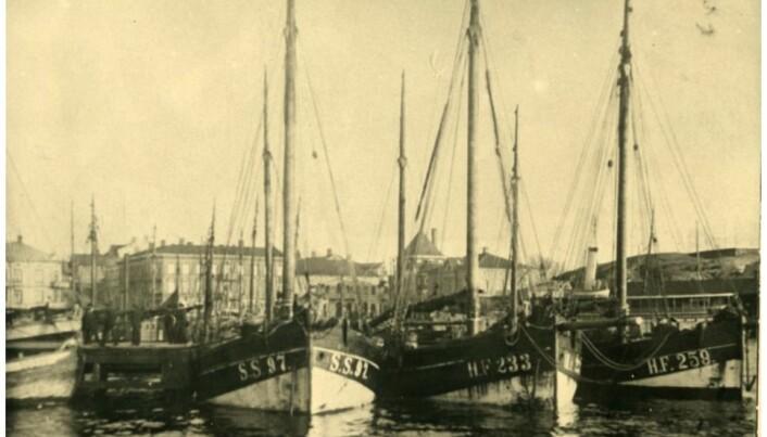 Tyske fiskebåter ligger i Strømstad havn i 1922, tungt lastet med sprit som skal smugles til Norge. Havnen var de norsk-svenske spritsmuglernes hovedbase og svensk lov forbød ikke virksomheten. Varene ble lastet over på raske norske smuglerfartøyer som ventet ved Grisebåene, sør for Hvaler, som da var internasjonalt farvann. Virksomheten var så omfattende at Strømstads havneavgifter ble mer enn fordoblet. Grand Hotell i byen var møteplass for norske «spritbaroner» og utenlandske selgere og kaltes på folkemunne bare for «Sprithotellet». (Foto: Gunnar Thorén, Strømstads museum)