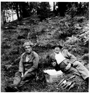 En svensk og en norsk grenseboer har møttes like etter krigen for sammen å tå seg en tår i det fri. Bildet er tatt i Vassbotten, lengst sør i Østfold. (Foto: Bohusläns museum)