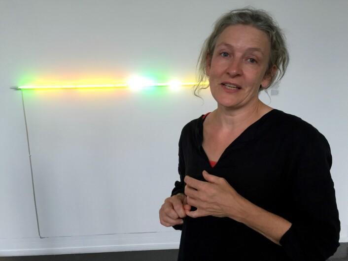 """Denne tynne lysstrålen er et av verkene på årets høstutstilling i Oslo. Noen vil kun se dette som et neonlys. Leder av juryen, Anne Karin Jortveit, mener at ved å lese tittelen """"Yellow – Jealeous, homage to Edvard Munch"""", får verket en helt annen betydning for henne. – Munch var opptatt av farger og sinnsstemninger. Denne tynne lysstrålen i verket til Per Hess har mye gult og grønt i seg. Farger som sier noe om voldsomme omkastninger i menneskesinnet. (Foto: (Siw Ellen Jakobsen))"""