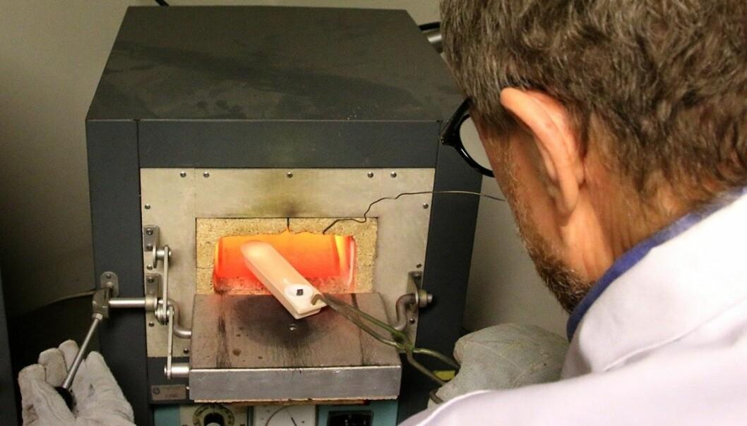 Overingeniør Pål Ulseth setter en kapell inn i den 900 grader varme ovnen. (Foto: Idun Haugan, NTNU)