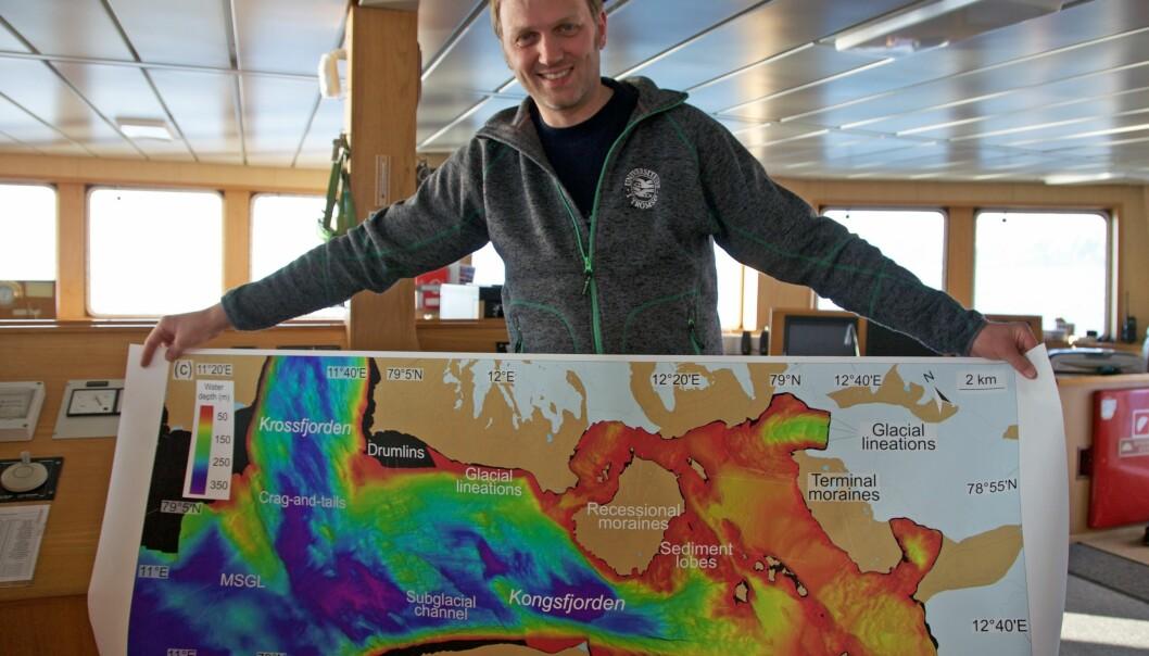 Matthias Forwick med et nytt kart over havbunnen i Kongsfjorden. Kartdataene er samlet inn og gjort tilgjengelig av Kartverket. (Foto: Karine Nigar Aarskog)