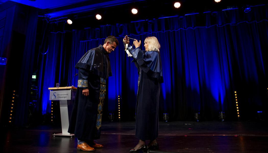 Klaus Mohn får rektorkjedet fra Marit Boyesen under rektorseremonien i Tjodhallen. (Foto: Mari Løvås / UiS)