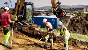 Gravemaskinen er helt uunnværlig i utgravingen. Mange tonn med jord og stein skal flyttes. Her er det arkeologene Colin Amundsen (t.v), Jon Reinhart Husvegg og Mari Samuelsen som jobber side om side med gravemaskinen.  (Foto: Elisabeth Tønnessen)
