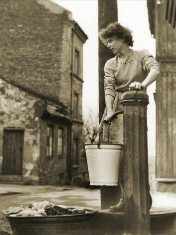 I gamle dager måtte du gå til vannposten etter vann. Fortsatt må du gå til jernbanestasjonen etter togskyss. Dette bildet er fra Enerhaugen i Oslo på begynnelsen av 1950-tallet. (Foto: Ukjent fotograf, oslobilder.no CC BY-SA 3.0)