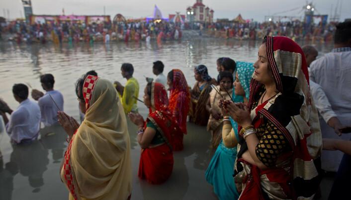 Hinduer utfører et religiøst ritual ved elven Brahmaputra i 2018. (Bilde: AP Photo/Anupam Nath/NTB Scanpix)