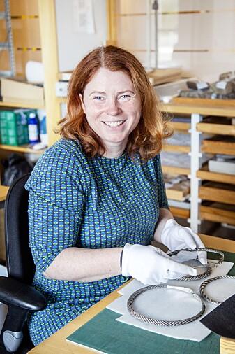 Linn Eikje Ramberg er arkeolog ved Arkeologisk museum, Universitetet i Stavanger. Her sitter hun med de flotte halsringene fra vikingtiden som ble funnet i Hjelmeland kommune. (Foto: Annette Øvrelid, Arkeologisk museum, UiS).