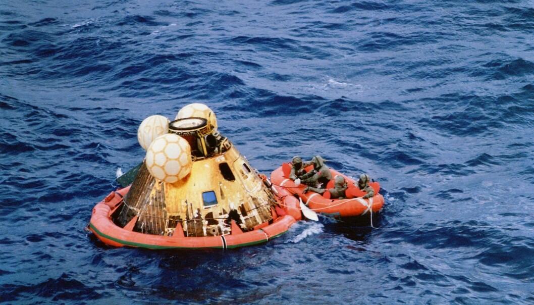 Astronautene venter på å bli plukket opp i helikopter. De har tatt på seg isolasjonsdrakter som skal hindre eventuell månesmitte. (Foto: NASA)
