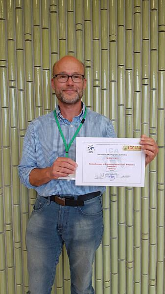 Førsteprisen ble tatt imot av seksjonsleder Yngve Melvær, også han er svært glad for at kartet nådde helt til topps under konferansen som samler noen av verdens fremste fagmiljøer innenfor kartografi. (Foto: Norsk Polarinstitutt)