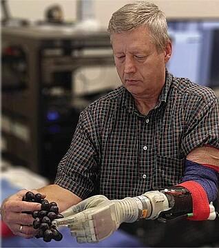 """Keven Walgamot har amputert en av armene. Her håndterer han druer med den nye protesearmen """"Luke"""". (Foto: University of Utah)"""