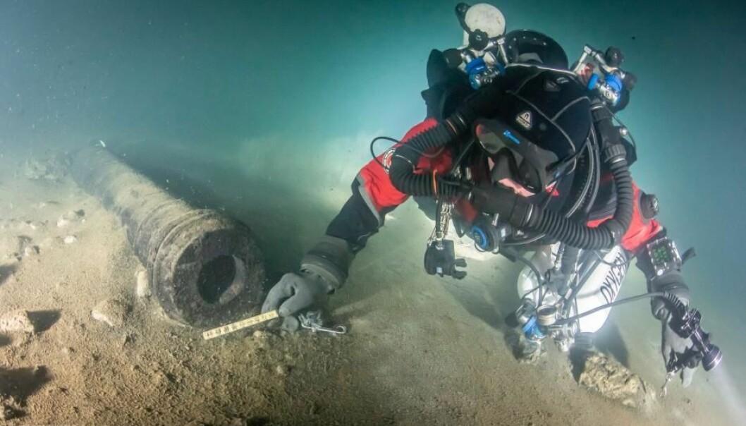 En dykker undersøker en av kanonene på skipsvraket. (Foto: Kirill Egorov / Ocean Discovery / Mars Project)