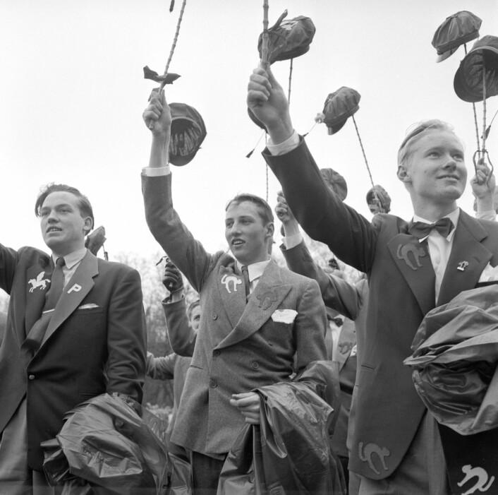 """Kong Harald som russ i på 17. mai i 1955. Tidene har endret seg. Det var ingen russedresser, men elevene hadde symboler på jakken, som viste at de gikk ut av Katedralskolen, bedre kjent som """"Katta"""". (Foto: NTB Scanpix)"""
