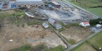 """Flyfoto av Tjora ved undersøkelsenes slutt i 2009. Gravfeltet er her helt fjernet. Vi kan se rester etter stolpene i langhusene i forgrunnen. (Foto: E. Torp """"Birdy"""")"""