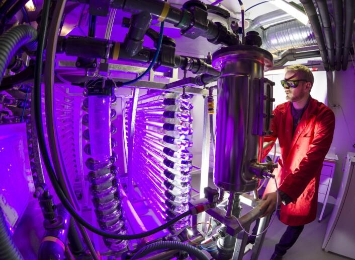 Denne fotobio-reaktoren rommer 250 liter med «algesuppe» og gjøre det mulig å oppskalere forsøkene betraktelig. Andreas Hagemann demonstrerer med rød belysning. (Foto: Thor Nielsen, SINTEF)