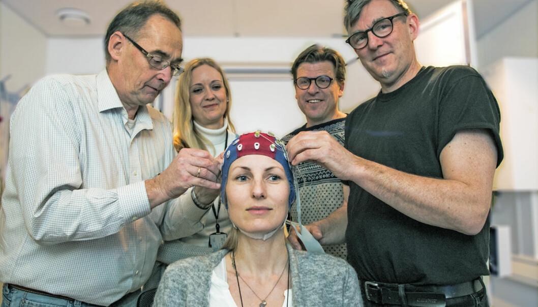 Pål Gunnar Larsen (f.v.), Anne-Kristin Solbakk, Torstein Meling og Tor Endestad ønsker å undersøke hvordan hjernesignalene kan kommunisere direkte med tekniske hjelpemidler. Her måler de hjernesignalene på Ingrid Funderud. (Foto: Yngve Vogt)