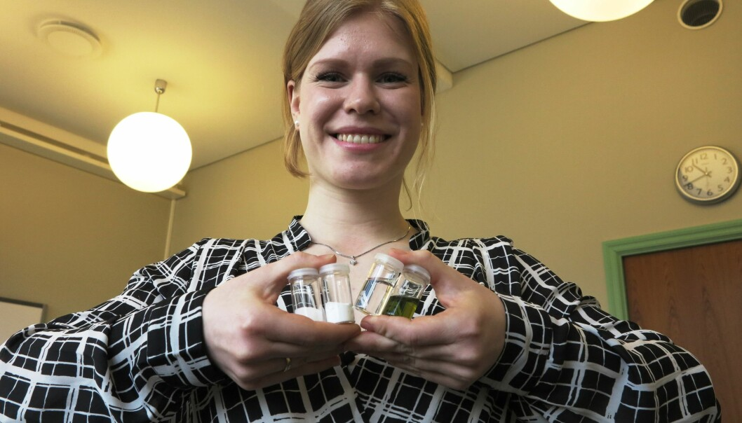 Kristine Opsvik Wikene holder fire prøveglass som inneholder (fra venstre) sukrose, glukose, den flytende blandingen av de to stoffene og NADES-blandingen med lysfølsomt fargestoff.  (Foto: Bjarne Røsjø, UiO)