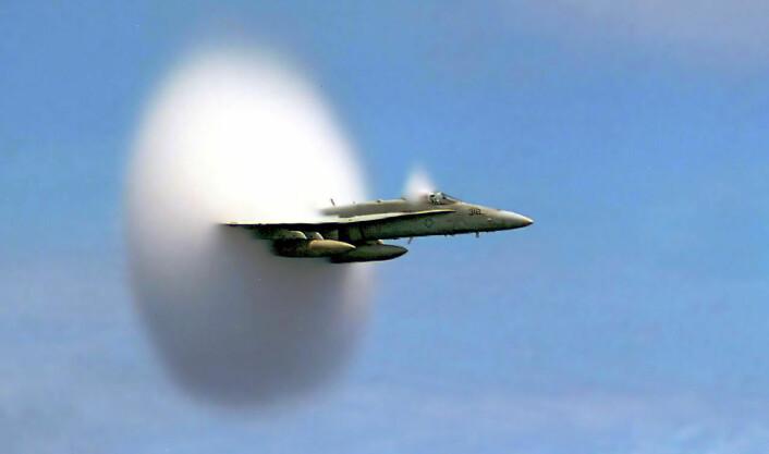 En F/A-18 Hornet jetjager bryter lydmuren utenfor kysten av Sør-Korea. Den hvite kragen bak flyet skyldes undertrykk like bak overtrykket i den supersoniske sjokkbølgen. I undertrykket blir vanndamp fra lufta brått kondensert til tåkedråper. (Foto: John Gay, U.S. Navy)