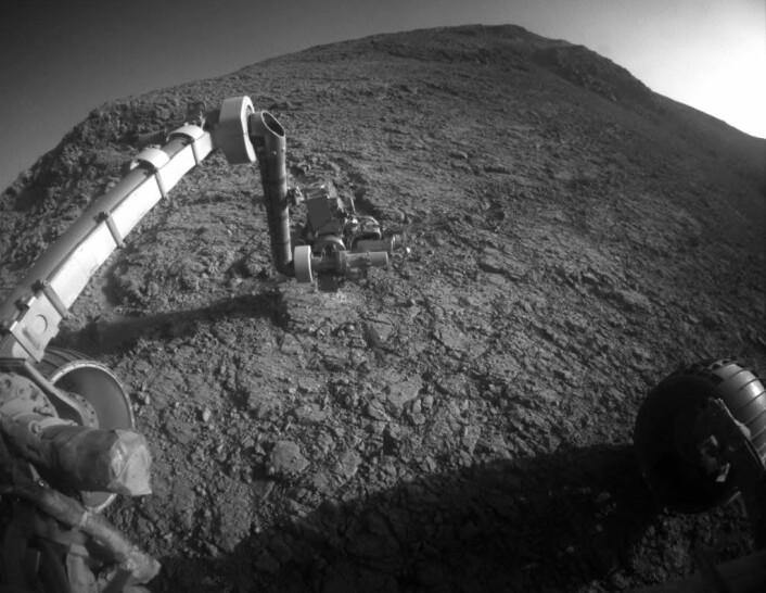 Dette bildet ble tatt av Opportunity den 5. januar 2016 på sørsiden av Marathon Valley, som skjærer gjennom vestkanten av krateret Endeavour. Armen ned mot bakken inneholder et kamera for mikroskopi av bergartene, et verktøy som skraper vekk den øverste overflaten og et røntgenspektrometer som analyserer de kjemiske bestanddelene i bergartene. (Foto: NASA/JPL-Caltech)