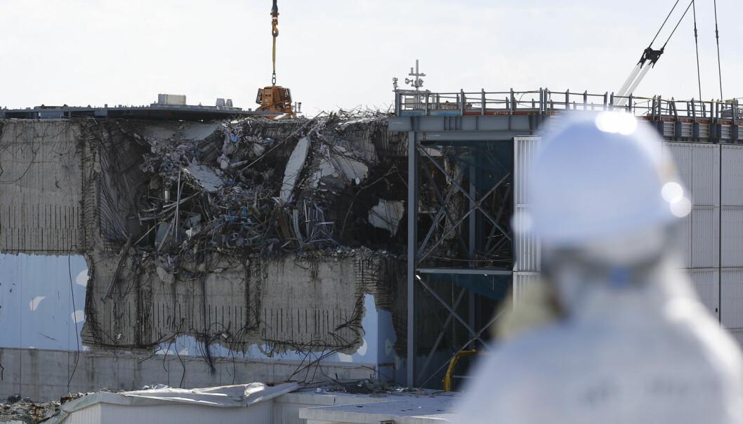En besøkende journalist ser på en av de skadde reaktorhusene ved Fukushima Daiichi-kraftverket i februar 2016.  (Foto: Toru Hanai/Reuters/NTB Scanpix)