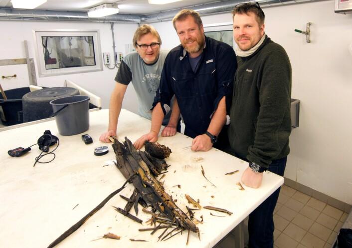 Geir Johnsen (til venstre), Jørgen Berge og Øyvind Ødegård undersøker trestokken om bord på forskningsskipet «Helmer Hanssen». (Foto: UiT)