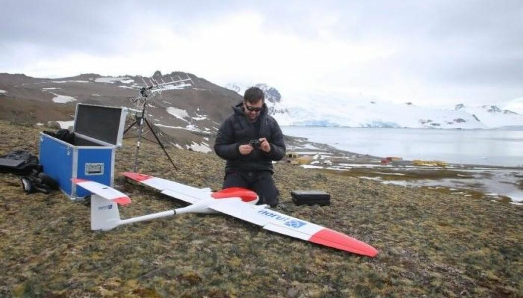 Seniorforsker Agnar Sivertsen gjør klart for flygning i Antarktis. I bakgrunnen skimtes den polske forskningsbasen Henryk Arctowski, hvor forskerne bor under oppholdet. (Foto: Andreas Tøllefsen)