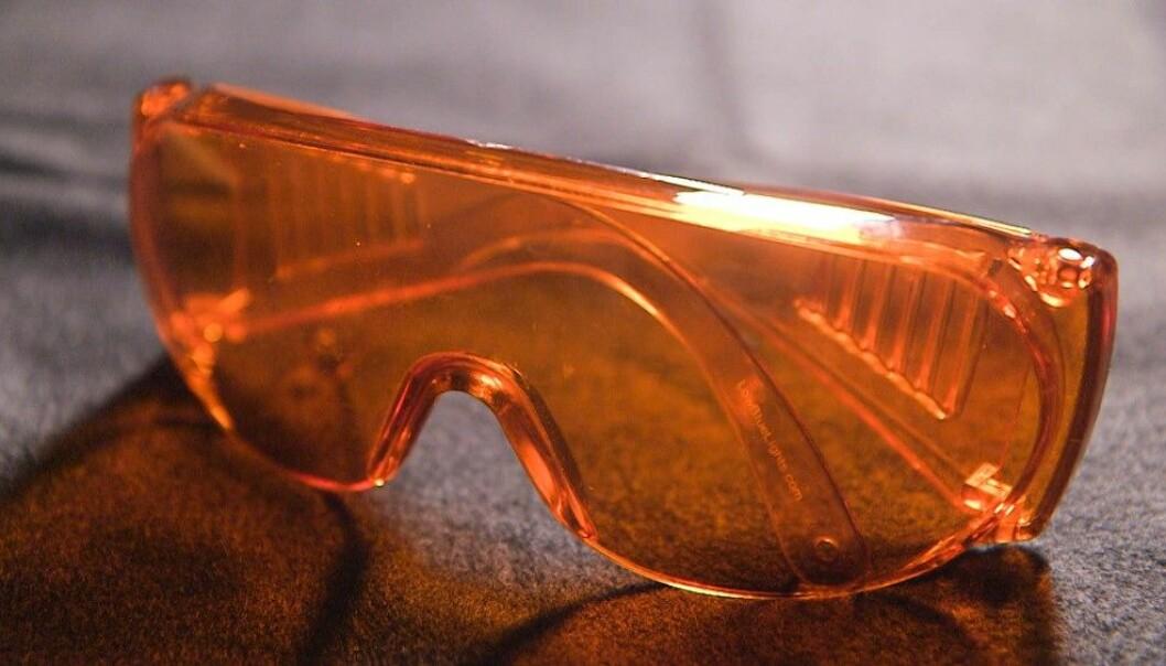 Slike oransje briller stenger ut det blå lyset, som forskere tror er med på å forlenge de maniske periodene hos bipolare. (Foto: Roger Myren/NRK)