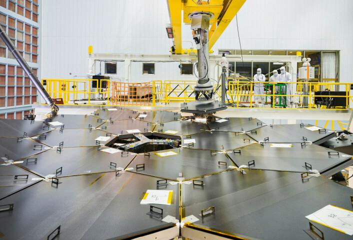En robotarm ble brukt til å sette på plass det siste av de 18 speilsegmentene i romteleskopet James Webb. Dette skjedde den 4. februar i det store renrommet til Goddard Space Flight Center i Greenbelt, Maryland i USA. (Foto: NASA/Chris Grunn)
