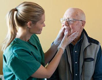 Tannlege Sara Bergstrand sjekker tennene på en eldre pasient.  (Foto: Håkon Størmer)