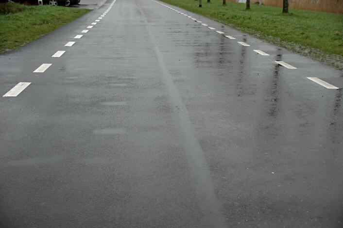 Etter et halvt år ser det ut til å være forskjeller: Til venstre på veien, der det ligger vanlig asfalt, har slitasjen laget dumper der vannet legger seg på en regnværsdag, mens bioasfalten til høyre på bildet ikke har den samme slitasjen. (Foto: Georg Mathisen)