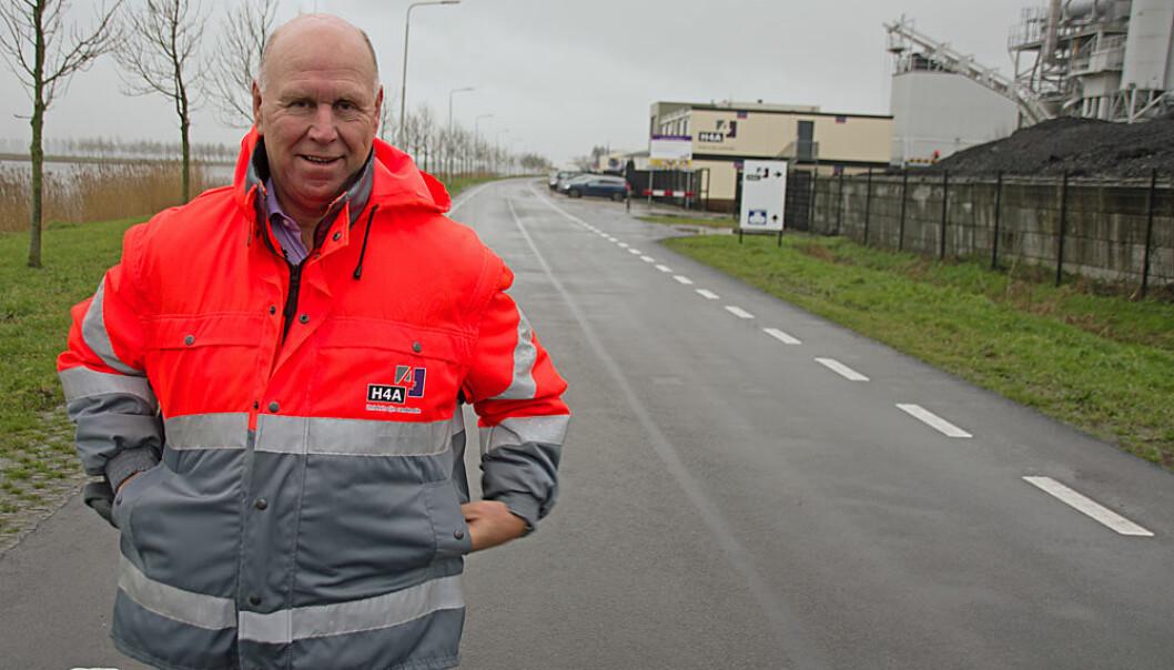 Den er verdens første – Ronald Verbruggen står på bioasfalten, som logisk nok ligger på veien rett forbi asfaltfabrikken. (Foto: Georg Mathisen)