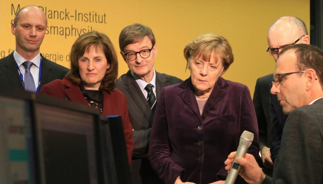Merkel og forskerne kikker spent etter resultatet, etter at forbundskansleren trykte på knappen.  (Foto: IPP, Norbert Fellechner)