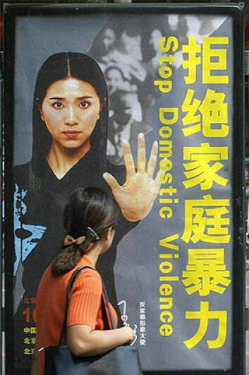 Modellen Wang Tong viser hva hun mener om vold mot kvinner på en plakat i den norsk-støttede organisasjonens informasjonskampanje. (Foto: ADVN)
