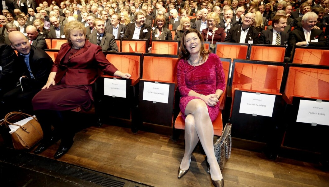NHO-leder Kristin Skogen Lund blir ofte avbildet med smykker, langt hår, og fargerike klær. Dette bildet er tatt på NHOs årskonferanse i 2015, sammen med blant andre statsminister Erna Solberg. (Foto: Vidar Ruud / NTB scanpix)