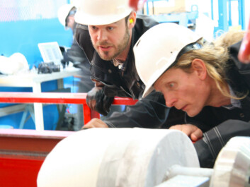 Knut Høyland (right), a SAMCoT professor, inspects the ice bullet with PhD candidate Torodd Nord. (Photo: Nancy Bazilchuk)