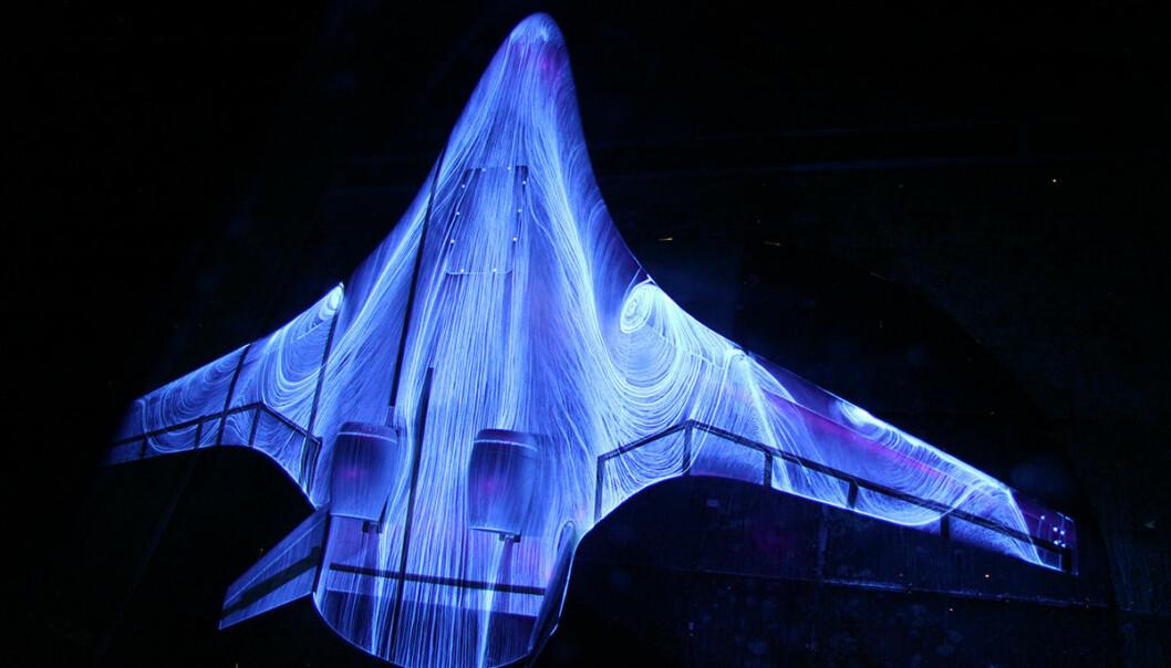Fluoriserende olje gløder og viser luftstrømmen rundt denne futuristiske flykroppen i vindtunnelen til NASAs Langley Research Center sommeren 2015. NASA utvikler ikke bare framtidas romskip, men også fly som sparer drivstoff og dermed slipper ut mindre CO2. (FOto: NASA Langley/Preston Martin)