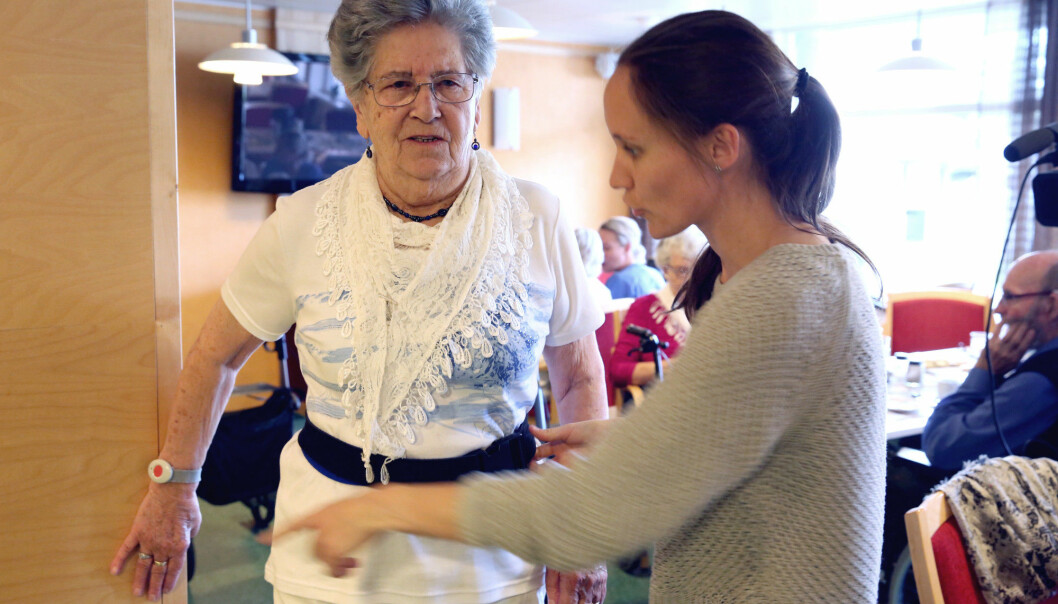 Skjoldvor Måsøval, resident at the Laugsand day care centre, is helped by a scientist to adjust the belt that will trigger an alarm if she is unlucky and falls. (Photo: Kjersti Fikse Ness, Adresseavisen)