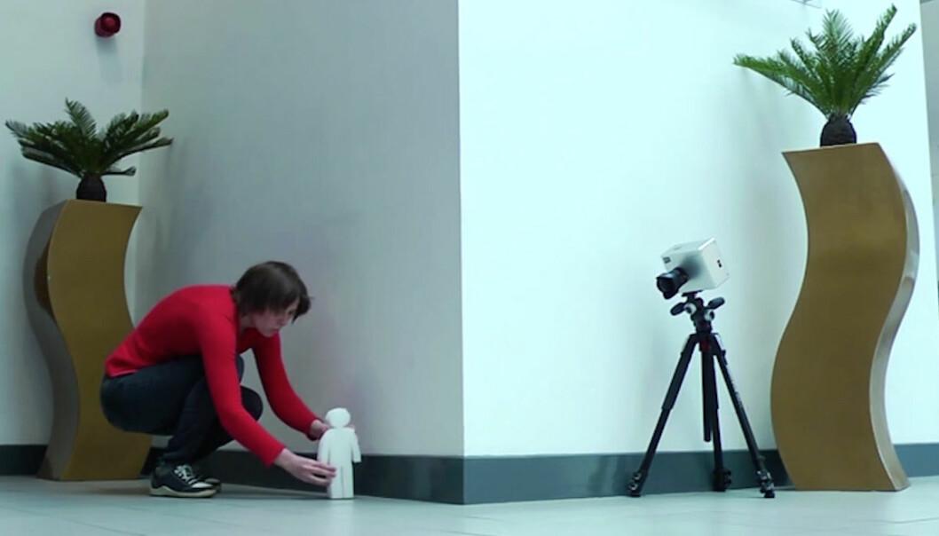 Genieve Gariepy fra Heriot-Watt University i Storbritannia stiller opp dukken som kameraet til høyre kan se rundt hjørnet. En lynrask laserpuls reflekteres av rommet og dukken. Refleksen sendes tilbake til gulvet foran kameraet, som fanger opp de enkelte lyspartiklene – fotonene – 20 milliarder ganger i sekundet. Slik kan et bilde av hva som er rundt hjørnet rekonstrueres i et dataprogram ut fra når de forskjellige refleksene treffer gulvet foran kameraet. (Foto: Fra YouTube-video av Heriot-Watt University.)