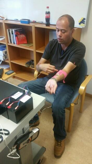 Bjarte Ellingsen, oppfinnerens sønn, prøver en prototype av mikrovibratoren som måler blodsukkeret på armen.  (Foto: Olav Ellingsen)