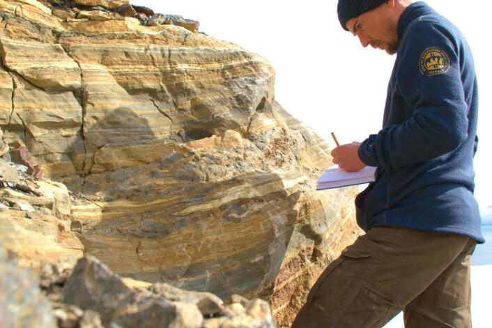 Fjellkjedeforskere klatrer over fjellrygger og forserer breer for å finne fram til den rette steinen. Her nyter Per Inge Myhre utsikten. (Foto: tatt med selvutløser av Per Inge Myhre / Norsk Polarinstitutt)