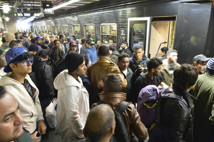 Flyktninger og immigranter venter på et tog til København på togstasjon i Flensburg i Tyskland 12. november. Men målet er Sverige, ikke Danmark.  (Foto: Carsten Rehder/DPA/NTB)