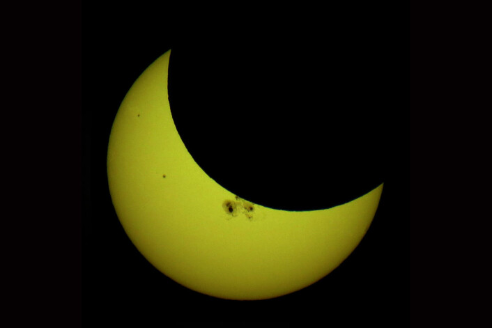 Oftest går månen litt over eller under solskiva ved nymåne, fordi banen er litt skjev. Her har månen delvis truffet solskiven. Det kalles en partiell solformørkelse, og er vanligere enn en total solformørkelse. Like ved kanten av måneskiven sees solflekker. Bildet er tatt 23. oktober 2014 i Minneapolis i USA. (Foto: Tomruen, Creative Commons Attribution-Share Alike 4.0 International license)
