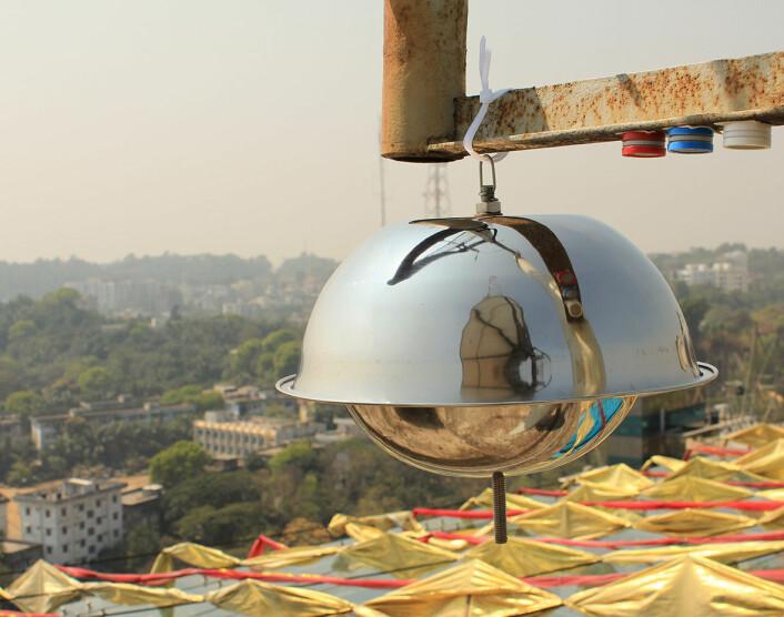 Bildet viser luftmålere inne i byen Chittagong i Bangladesh. Den store «metalldomen» samler inn luftprøver for analyse av miljøgifter, mens de tre små sylindrene måler nitrogendioksid (blå), svoveldioksid (rød) og ozon (hvit).  (Foto: Scott Randall/NILU)
