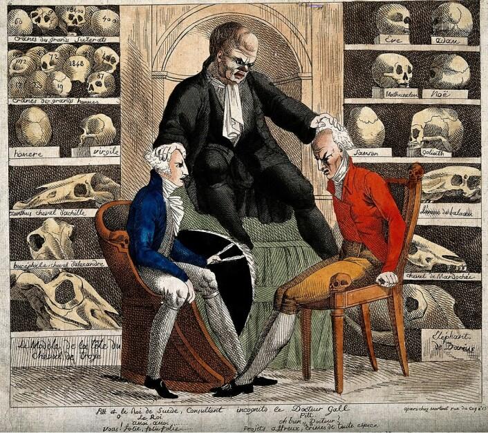 En karikatur av dr. Gall fra 1806. Omringet av berømte hodeskaller, undersøker Gall hodene til William Pitt den yngre og Gustav IV Adolf, kongen av Sverige. Tegnet av  (Foto: (Bilde: Wellcome Library/Wikimedia Commons.))