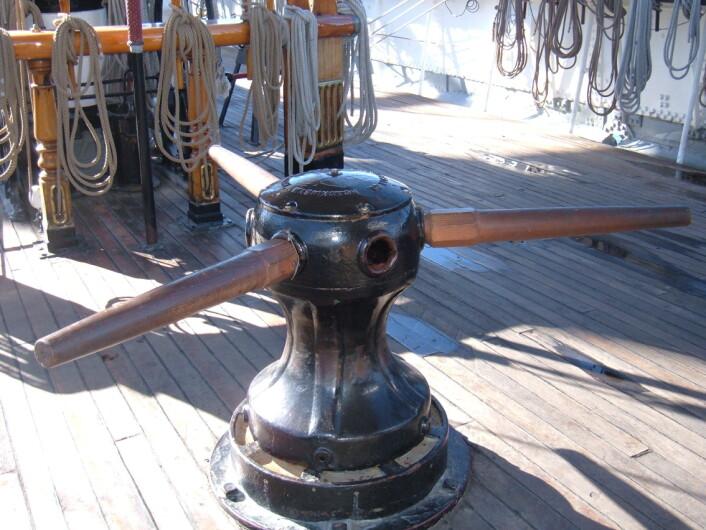 For lesere som ikke er kjent med skipstekniske begreper; dette er et eksempel på et gangspill, gjerne kalt forhalingsvinsj. Hånddrevne gangspill har lange, løse spaker, som stikkes inn i huller i toppen av spilltrommelen, med én eller flere mann på hver. (Foto: Wikimedia Commons)