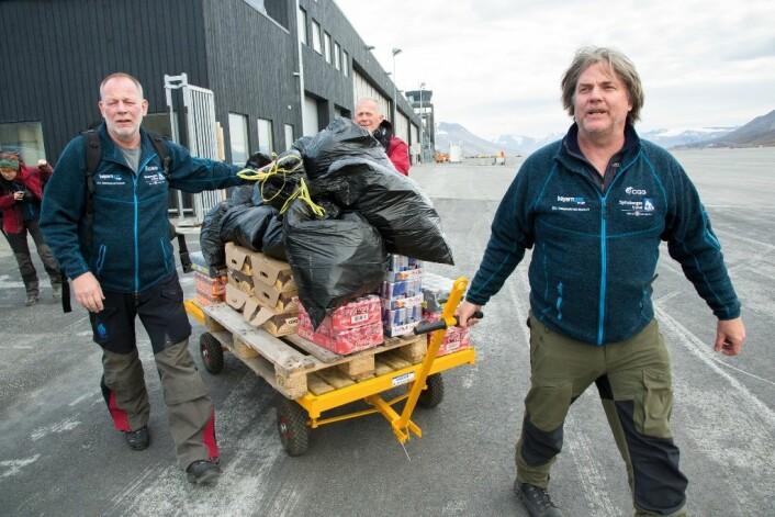 Øyvind Enger (f.v.), Stig Larsen og Jørn Hurum sørger for at avsindige mengder med Coca Cola og energidrikker står klar til helikoptertransporten fra flyplassen i Longyearbyen.  (Foto: Yngve Vogt)