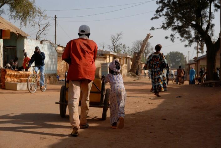 En mairuuwa og dattera i husholdet vannet skal levers til på veg gjennom boligkvarteret med i vogn vann.