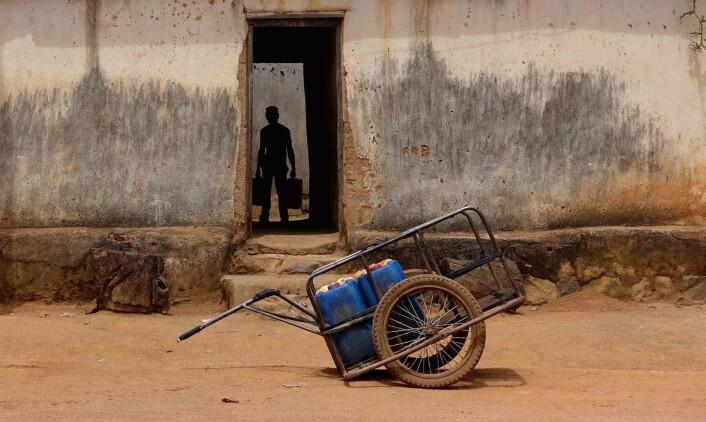En mairuuwa har levert noen kanner vann i et hushold. Trillevogna venter på utsiden.